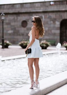 Kenza Zouiten is wearing a pale blue dress from Finders Keepers, bag from Saint Laurent, shoes from Jennie-Ellen and sunglasses from Prada