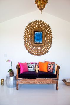 just a lovely vignette with bold & beautiful antique gold mirror, wood bench with purple pink orange pillows, white walls ceilings floors, rustic and ethnic with a sleek modern crisp white