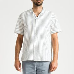 "The Ron keeps it casual with a relaxed camp-collar and cool, lightweight Japanese fabric. The body is a slightly oversized fit. Topped off with a chest patch pocket, side vents, and roomy back box pleat for the perfect Americana summer look.  With the Blue stripes laid on the White short sleeve shirt, The Ron is the perfect shirt for the everyday casual wear and is versatile for a variety of style and color combinations. The vertical stripes on the shirt also give off the ""slimming effect""…"
