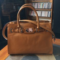 Authentic MICHAEL Michael Kors Hamilton handbag Authentic MICHAEL Michael Kors Hamilton handbag.  Beautiful tan buttery soft leather with goldtone/leather shoulder strap with 11-inch drop.  Double handles with 5-inch drop.  Magnetic snap closure.  Gold-tone hardware.  Interior center zip picket as well as side zip pocket and two side slide pockets.  Dimensions:  14.5 inches wide X 10.25 inches tall X 5.5 inches deep. MICHAEL Michael Kors Bags Shoulder Bags