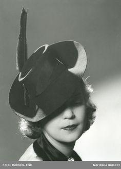 Porträtt av kvinna i hatt med ripsband, penna och uppvikt brätte. Foto: Erik Holmén, 1941.