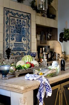 I adore everything about this European kitchen. The antique tile panel and old stone...Gorgeous!