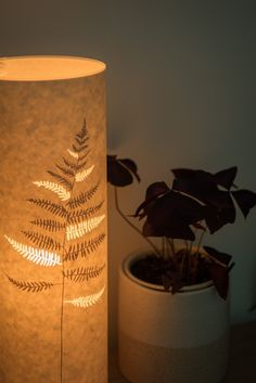 Glowing cylindrical fern table lamp made from lasercut parchment by Hebden Bridge designer/maker – Hannah Nunn. We ship worldwide from our website www.hannahnunn.co.uk