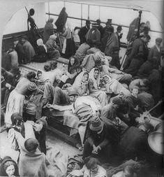 Immigrants on Ellis Island. Photo by William H. Rau. Public domain.