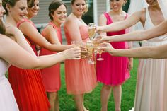 The bridal party in mismatched pink and coral bridesmaid dresses drinks champagne with the bride before ceremony.