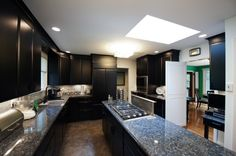 Black kitchen cabinets with stainless appliances and granite counter-tops.