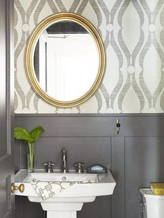 We are always a big fan of patterns used in a powder room. Even though the space is small, a bold print can make a big statement. Take this beautiful printed grass cloth wallpaper and painted wainscoting for instance. The design works well in this space since the color palette is neutral.