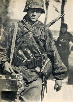 A soldier of the Waffen SS armed with a K98k rifle and hand grenades, is bringing up a can of ammo.