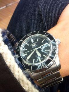 日本を代表する、いや、世界を代表する腕時計ブランドといえば、SEIKO。このブランドの果たした役割については、色々熱く書きたいこともあるのだけれど、今回は最も長く作られ続け、愛され続けるSEIKO 5について。 SEIKO 5は1963年から作られ続けているモデル。機械式の腕時計は、クォーツショックのあと、薄く、軽く、電池で動くことが時代の最先端、ということで、国内向けの生産は一度やめてしまったところも多く、その中でこのSEIKO 5は止まることなく作り続けられてきた。 これは凄いことだと思う。 そうして止まらず生き残れたのは、販路を国内ではなく海外に移したから。だから、一応国内の販売ラインナップからは消えている。海外では格安で電池が要らず、結構タフに動いてくれるSEIKO 5は細く長く愛され続けた。特に中東など。 海外で販売することで、国内ではSEIKOという名を持つ以上やりにくいデザイン上の思い切ったものや、どこかの時計に似ているものなど、また、デザイナーが自分の時計への想いをぶつけたものなど、大量生産出来るからこそ作れる思わぬ名作が数多く生まれている。…