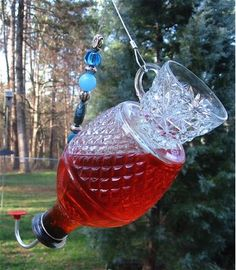 Large capacity yet graceful hummingbird feeder with decorative teacup Antique cut glass bottle is turned into a functional feeder with artful design. Lab-quality large rubber topper along with a feedi Glass Hummingbird Feeders, Humming Bird Feeders, Hummingbird Food, Glass Flowers, Glass Birds, Art Flowers, Glass Garden Art, Glass Art, Garden Totems