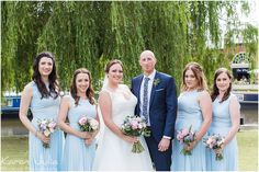 bride and groom with bridesmaids wearing pastel blue dresses near Castlefield Rooms