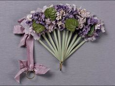 Bouquet fan, purple and lavendar silk violets with glazed green leaves attached to green silk leaf with lavendar pinked silk edging, pale green wood sticks, decorative brass ring, lilac silk ribbon to left ties in bows at top. Antique Fans, Vintage Fans, Hand Held Fan, Hand Fans, Sweet Violets, Ribbon Work, Silk Ribbon, Arte Floral, Pink Silk