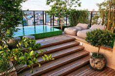 Jardim relaxante em cobertura. Piscina e vidro ganham charme com muitas plantas e madeira. https://www.homify.com.br/livros_de_ideias/30589/10-jardins-estilo-espaco-lounge-para-relaxar