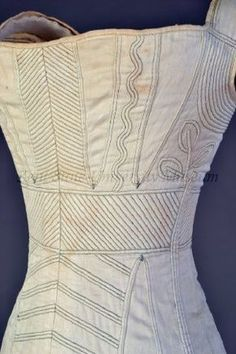 """""""Corset American or European, ca. 1820 White cotton corded and stitched in green; bone grommets This corset demonstrates the slightly lowered waistline of the 1820s. The decorative cording serves as the stiffener."""""""