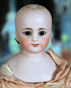 """10.5"""" early Bebe by Simon Halbig in a fabulous French style outfit. She has a perfect solid domed bisque shoulder head marked S 3 H on the lower edge of the front shoulder plate. She has beautiful fine painting with set paperweight eyes, a closed mouth, pierced ears and a blond mohair wig. She is on an early gusseted kid leather body with bisque forearms and a chunky girth. She wears antique undies and a fabulous Bebe silk dress with matching bonnet and leather shoes. These early dolls were…"""