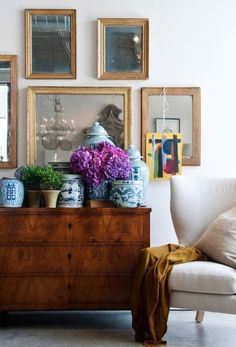 beautiful vignette with antique chest, lovely art wall, blue and white chinoiserie porcelain | purple hydrangeas and a contemporary wing chair in natural linen | pretty!