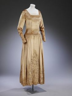 Wedding dress worn by Maud Cecil, 1927. When she married Greville Steel in November, metallic lames, shell-pink and pale-gold were popular choices for brides and eveningwear alike. Maud, the daughter of the MP Sir Evelyn Cecil and a recent graduate of London's Slade School of Fine Art, chose just such a light, golden shade for her wedding dress.  Maud's bridesmaids walked in pairs, each pair wearing dresses of gradating gold concluding in the tone of the bride's own dress.