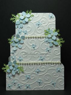 Quite decorative wedding cake card - uses an embossing folder on rounded rectangle shapes, and is then decorated with punches