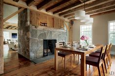 """""""There was a lot of texture already present here,"""" Groves says of the dining room at the renovated Connecticut barn. """"So we chose a very simple table and chairs—wood themselves, in order to relate to the surroundings—and a customized chandelier."""" A flagstone fireplace topped with wood cabinets anchors the space."""