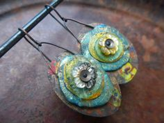 Rustic layered earrings with salvaged tin, polymer cornflakes, gold leafed tin, Roman glass, carved mop flowers. fancifuldevices