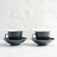 Pair of handthrown porcelain & white stoneware espresso cups & saucers with coloured glaze. Due to their handmade nature, each cup and saucer has variations, imperfections and fluid patterns on the glaze lending a unique natural quality.