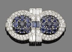 A sapphire, synthetic sapphire and diamond double clip brooch, circa 1935  Each clip of circular design, centrally-set with circular-cut and baguette-cut sapphires, within a brilliant and baguette-cut diamond surround, diamonds approx. 2.75cts total, length 4.6cm