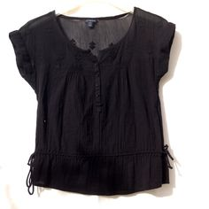 Black AE Top Short sleeve top by American Eagle. Has two small toes on either side towards to bottom, a small slit on the top as part of the neckline, along with buttons half way down the front. Back has lace like design. Semi sheer. American Eagle Outfitters Tops Tees - Short Sleeve