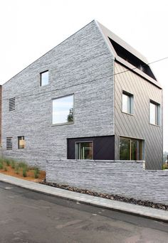 Wall House in Brussels by AND'ROL. Precast concrete lintels used as masonry, with oozing mortar at horizontal joints. Other walls are fiber cement panels.