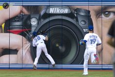 Blue Jays Rasmus slams into an outfield wall banner while catching a fly ball off the bat of Angels Aybar during their American League MLB baseball game in Toronto. FRED THORNHILL/REUTERS