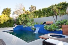 Designer Jeff Troyer remodeled this outdoor spa area, raising and tiling the pool and adding a waterfall. After the landscaping was thinned out, a seating area was created above the blue-tiled pool and hot tub.