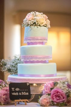"""""""Katie at Orange Blossom Cake Company made our cake. We had a rounded 3 tier, duck egg blue colour with lilac ribbon and lace wrapped around each tier. We had a Kate topper made from our florist, Rosie, at A Vintage Wedding to tie in with the rest of our flowers."""""""