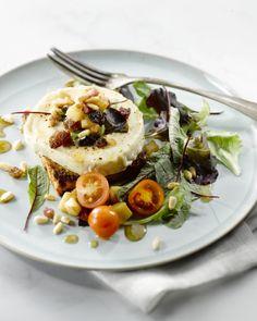 Een echte klassieke salade: lauwe geitenkaas met spekjes, appel en rozijnen. Het lekkerst geserveerd op een krokant plakjes rozijnenbrood.