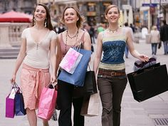 three young women wearing, and shopping for, apparel