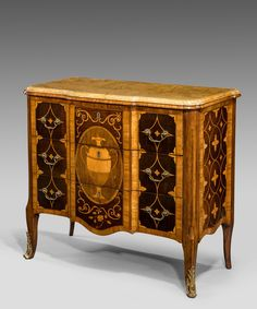 An Adam marquetry veneered commode. An elegant George III Adam period harewood and rosewood veneered breakfront commode with marquetry inlay; the well figured siena marble top above three drawers which are inlaid with central Neo-classical vase on rosewood ground set within a border of laurel leaves flanked by panels of harewood inlaid with boxwood in a diaper pattern and stylised flower heads; the sides veneered in harewood and inlaid with boxwood in a diaper pattern; raised on elegant ...