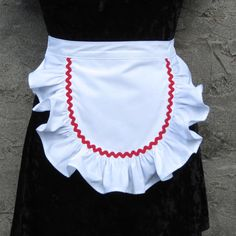 This is a sweet & sexy little white ruffled apron- perfect for hostesses, pinup photos or maids. Made without a pocket for a smooth fit, the half apron has rounded edges with a wide ruffle as well as red rickrack trim. Meant to be easy-care, this is made from an easy-care