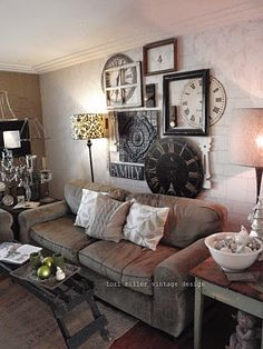 Shabby Living Room...wall of clocks & old frames...comfy sofa, textured walls, rug, & soft pillows...