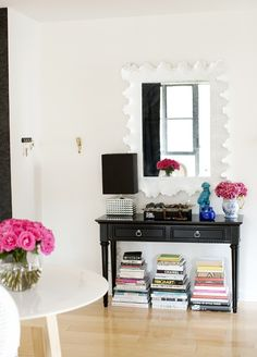 A lovely entry way table + books stacked on the floor under.