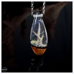 A small forest of Glowing Thorns trapped within a crystal clear iridescent drop. ◄ Pendant Information ► Dimensions (inches): 2.5 (H) -- 1 (W) -- 0.38 (D) Weight (grams): 12.6 Wood Species: Hawthorn A