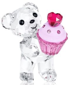 Sweet celebrations. Welcome a newborn into your lives with this expressive Kris bear in beautifully faceted Swarovski crystal. Holding a cupcake in Rose crystal topped with crystal chatons and a Ruby