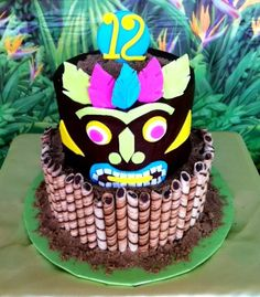 Tiki cake for my son's 12th birthday!  Buttercream icing with fondant details. Pirouette cookies on the bottom tier.
