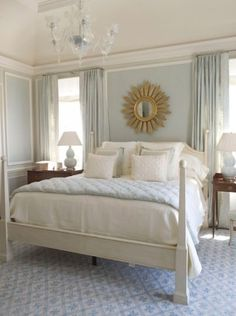 James Michael Howard - Lovely blue french bedroom design with white cream poster bed, blue linen drapes curtains panels, blue rug, blue bedding, blue throw pillows, sunburst gold mirror, white gourd lamp, French white chair with upholstered seat and antique table nightstand! Blue gray paint wall color. Blue gold gray white cream brown bedroom colors.