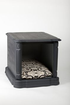This cozy little pet bed has been created out of a vintage end table. The door was removed and the inside was painted a light gray. The outside has
