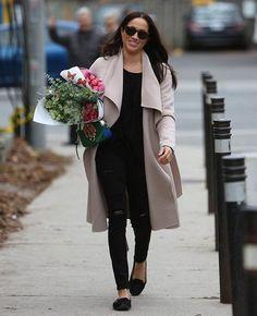 O estilo de Meghan Markle. Maxi casaco cinza, t-shirt preta, calça preta skinny com rasgo no joelho, sapatilha preta