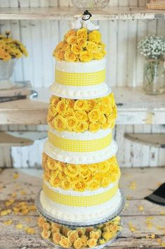 Adorable three layers wedding cake with yellow roses and a pair of love birds.