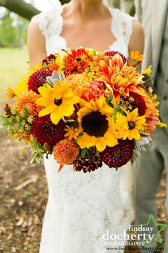 Autumn bridal bouquet in yellow, orange and red featuring sunflowers, black-eyed susans and dahlias. Designed by Love 'n Fresh Flowers.