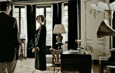 Coco Chanel black drapes against white wall.