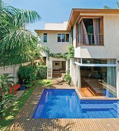 Casa assimétrica, janela de vidro e piscina com deck