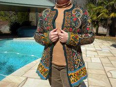 This elaborate pattern draws on Norwegian folk motifs to embellish this ingeniously shaped long fitted jacket.