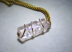 A pink rhombus of Icelandic spar optical calcite crystal, wrapped with gold filled wire. This comes with a 24 inch gold filled chain. Like many Iceland spar specimens, this one has surface prisms.