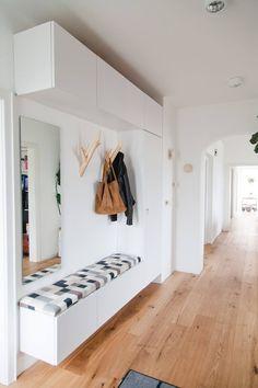 →102 Fotos para Renovar seu Hall de Entrada - Decostore. Piso de madeira, armario planejado branco, pendurador, cabideiro, espelho retangular, futon, parede branca.
